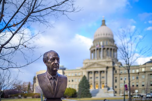 Bronze bust located in park near historic Idaho State Capitol with columns and dome against cloudy blue sky in Boise