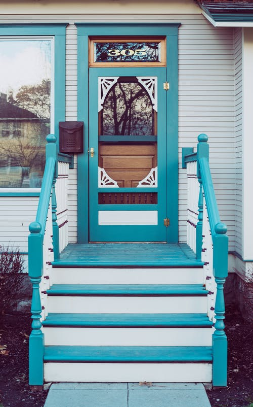 Blue colored wooden stairs and door of aged house in countryside on sunny day