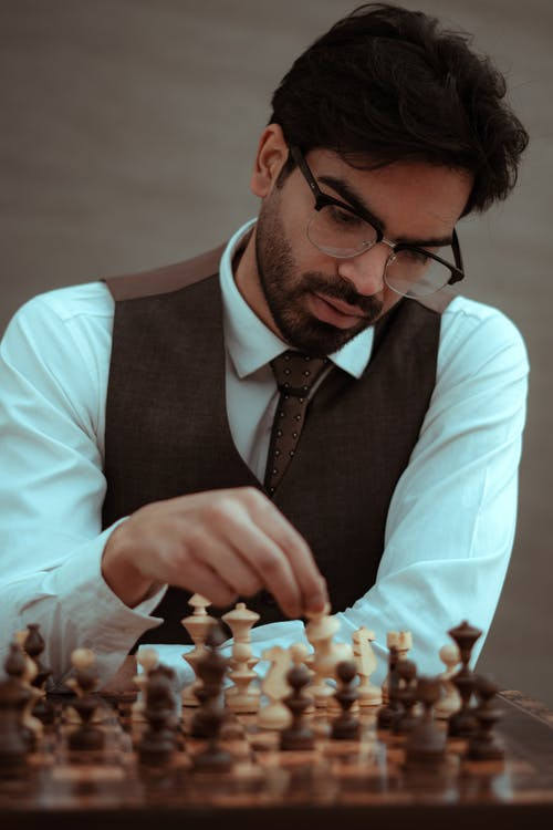 Focused bearded male in classy suit and eyeglasses playing chess game in studio