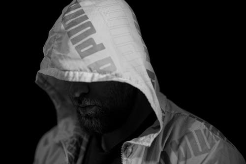 A Grayscale of a Man Wearing a Hooded Jacket