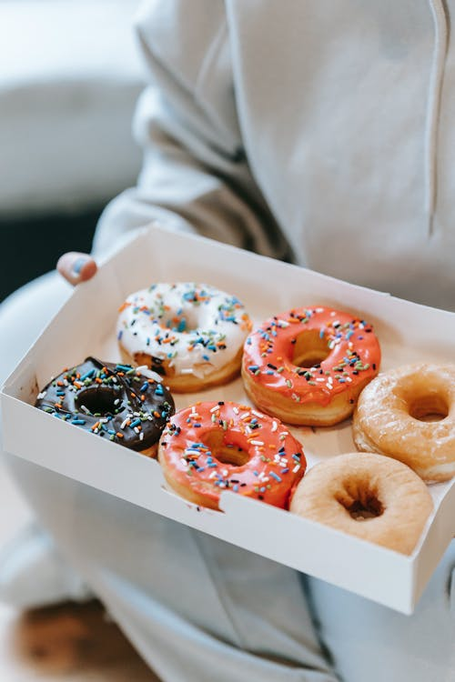 Crop unrecognizable person demonstrating box with delicious doughnuts