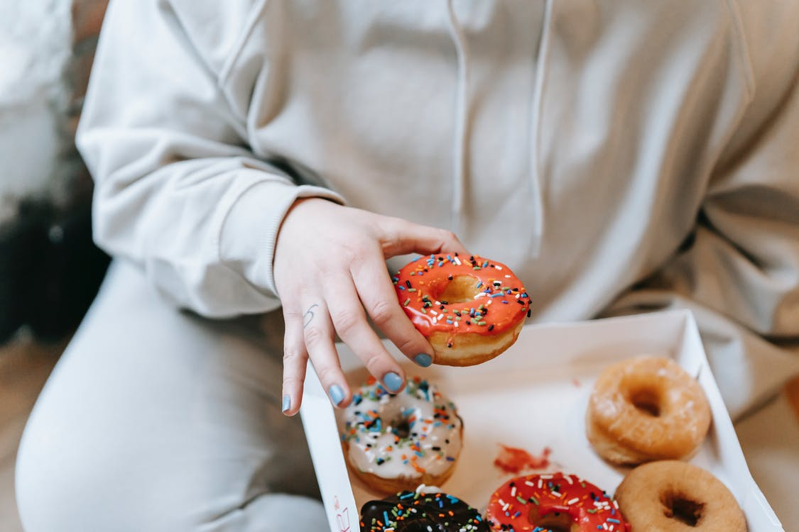 Crop faceless woman taking appetizing donut from box
