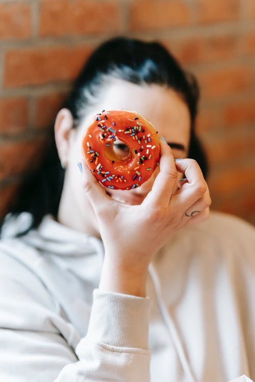 Happy blurred female in casual clothes looking through sweet fresh doughnut hole and leaning on brick wall