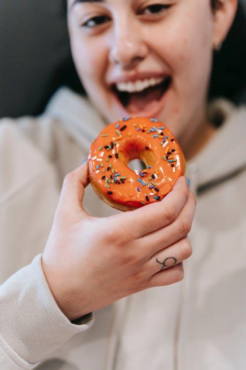 Crop joyful woman enjoying sweet donut