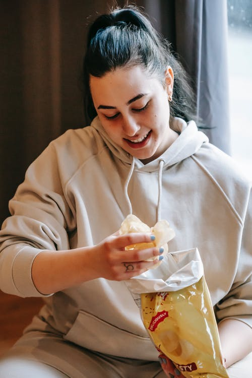 Smiling plump female wearing comfy hoodie eating crispy yummy potato chips while sitting in light room