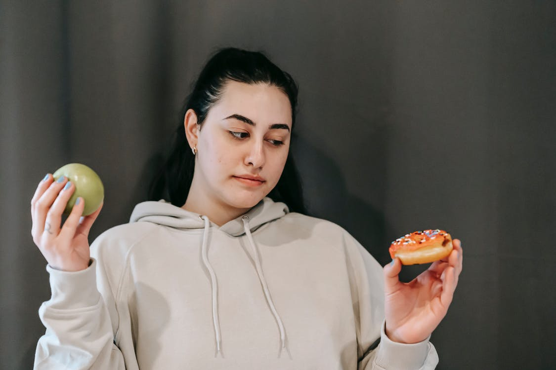 Thoughtful woman choosing between green apple and sweet donut
