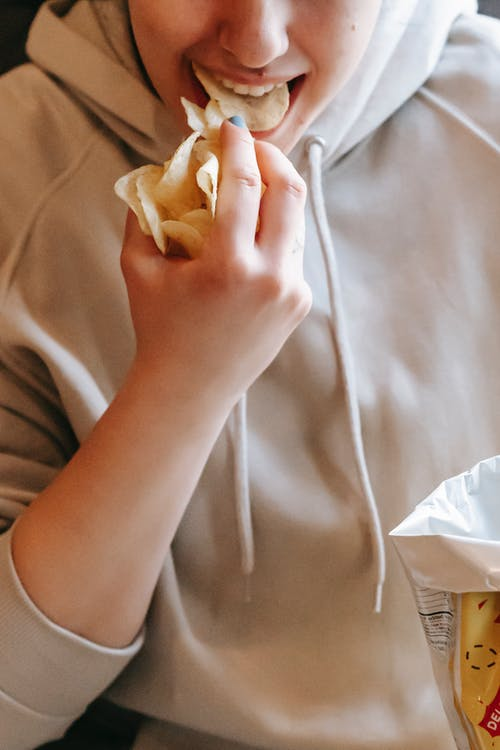 Crop female in comfy hoodie eating tasty savory potato chips in light room