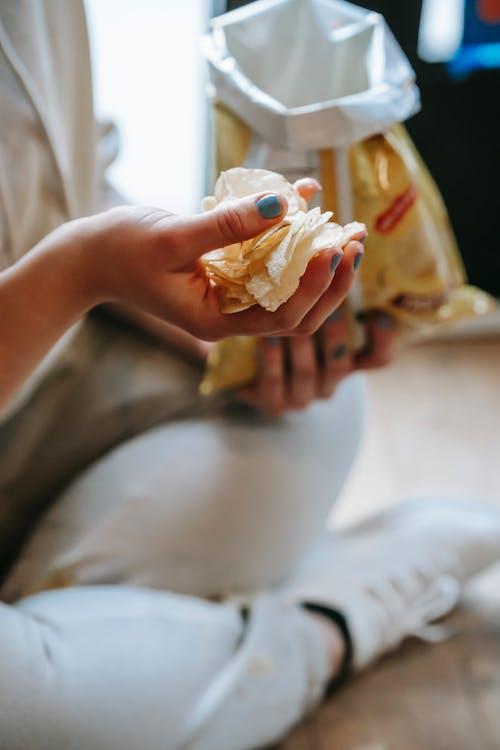 Crop unrecognizable plump woman eating yummy potato chips