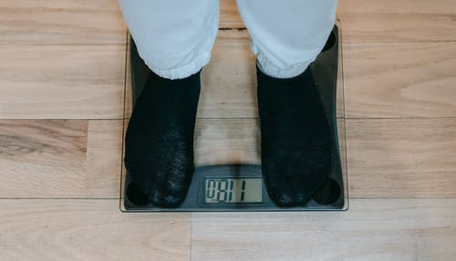 From above of crop unrecognizable plus size person in casual clothes standing on weighing scale on wooden floor