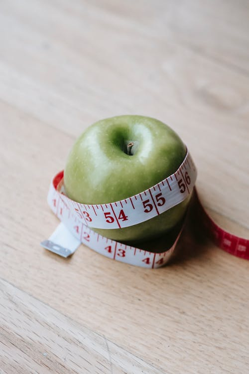 Green apple with measuring tape on table in kitchen