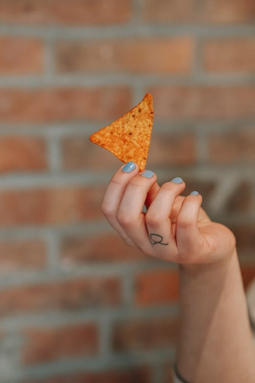 Crop woman with corn chip in hand