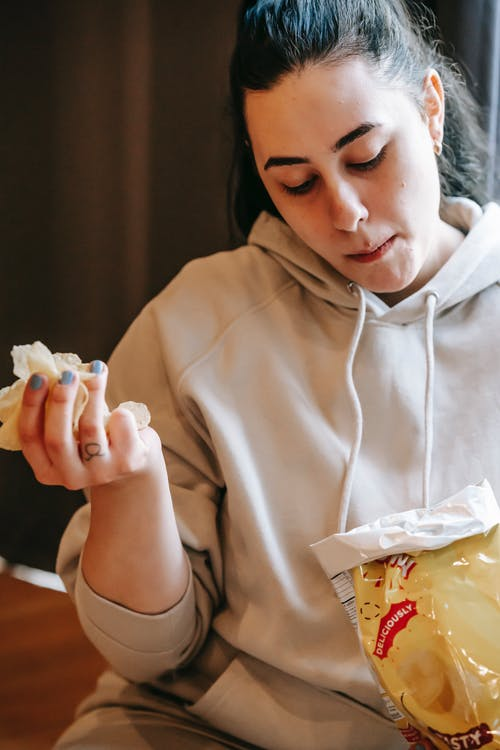Ethnic plus size woman eating chips in room