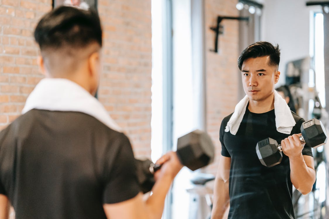 Active Asian male with towel lifting heavy dumbbell and looking in mirror while exercising in modern gym with brick wall
