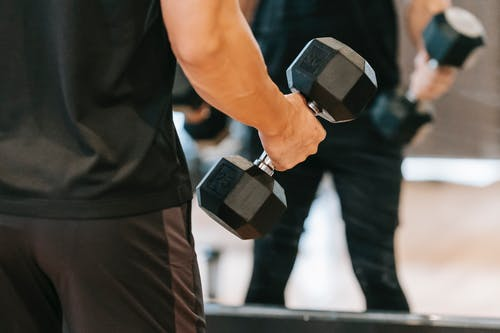 Crop man with dumbbell in gym
