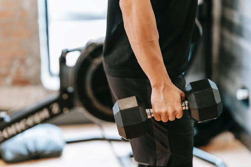 Side view of unrecognizable muscular male in black activewear lifting heavy weight while training in spacious fitness studio on blurred background