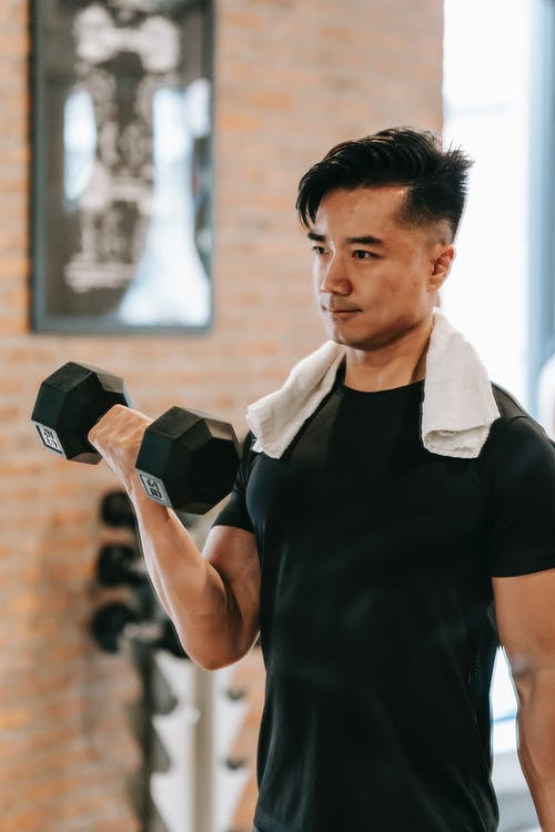 Muscular Asian man training with dumbbell