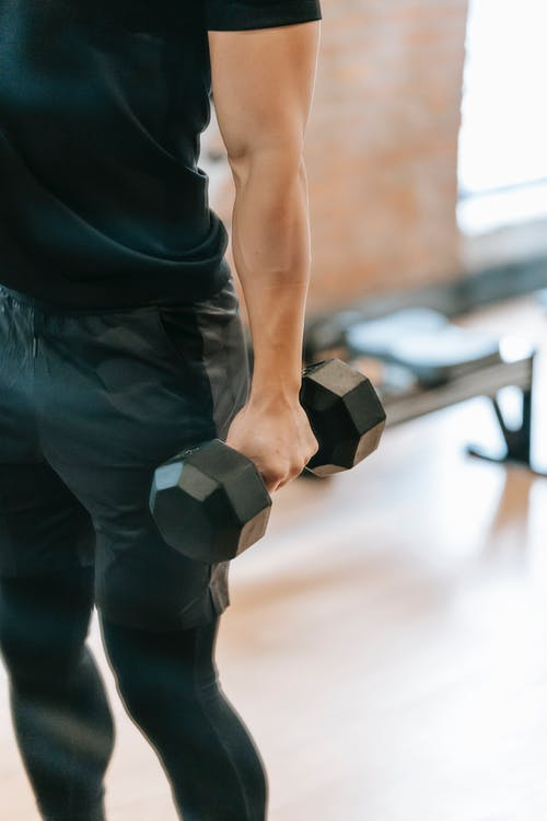 Unrecognizable muscular male in black sportswear lifting heavy dumbbell during weightlifting workout in light gym with bench on blurred background