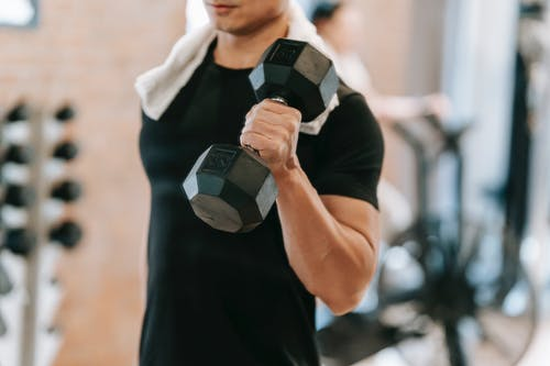 Unrecognizable strong male with towel wearing black activewear lifting heavy dumbbell during intense training in fitness studio with special equipment on blurred background
