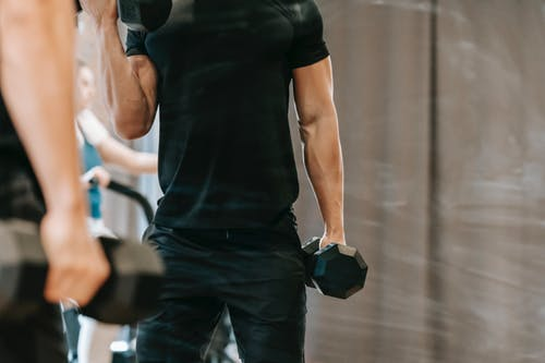 Unrecognizable muscular male in black sportswear pumping biceps with heavy metal dumbbells near mirror during workout in modern fitness studio