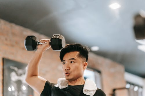 Muscular Asian man lifting dumbbell in gym