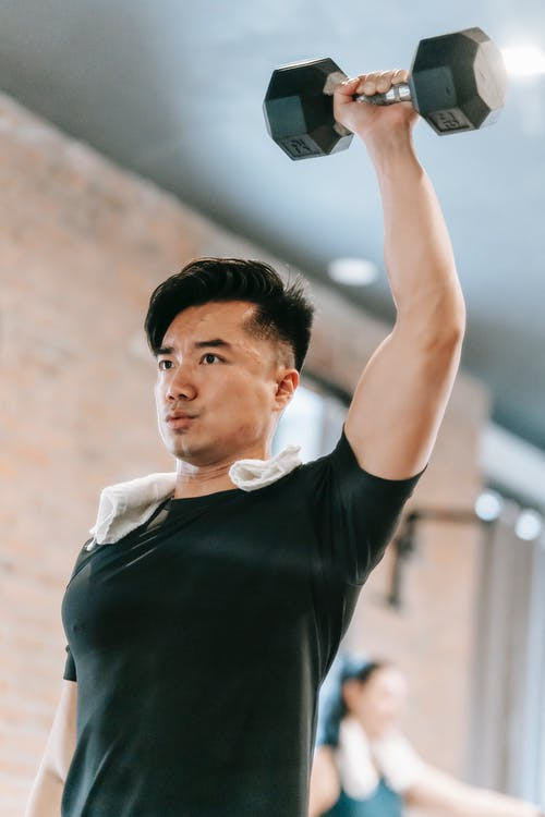 Sportive Asian male in black sportswear with raised arm lifting metal dumbbell while training in fitness studio with woman on blurred background