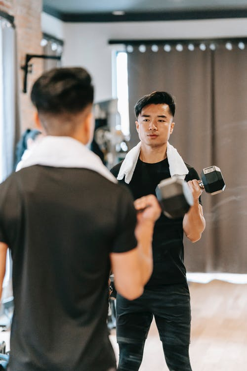 Determined Asian male in activewear with towel doing dumbbell curls while standing near mirror during fitness training in modern spacious gym