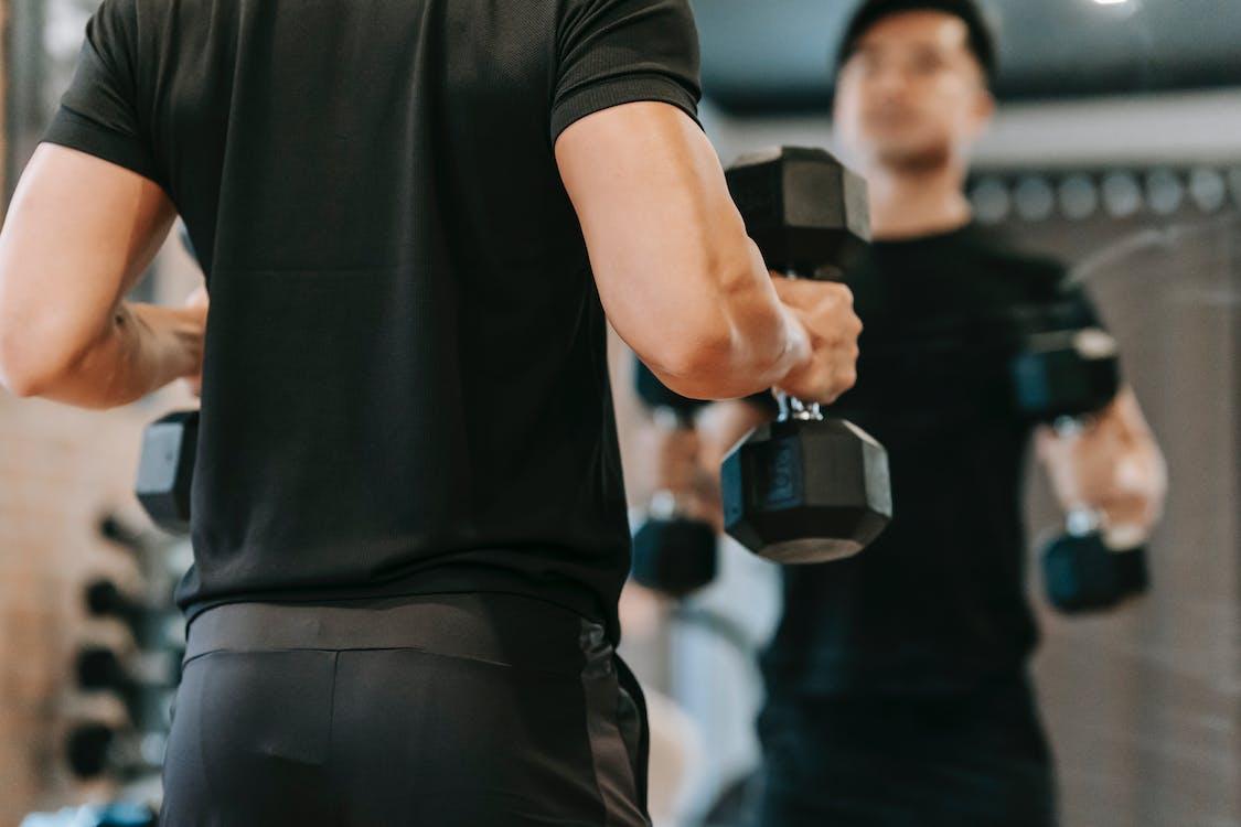 Crop sportsman with dumbbells in fitness studio