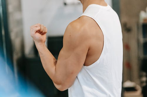 Side view of unrecognizable muscular male in white sportswear standing with bent arm while showing bicep during workout in gym on blurred background