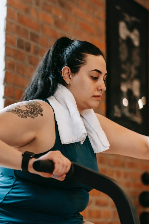 Side view of active plus size ethnic female with towel training on cross trainer machine during workout in modern gym