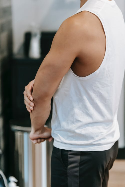 Crop sportsman with muscular arm in gym
