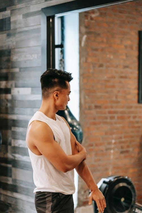 Muscular Asian man near mirror in gym