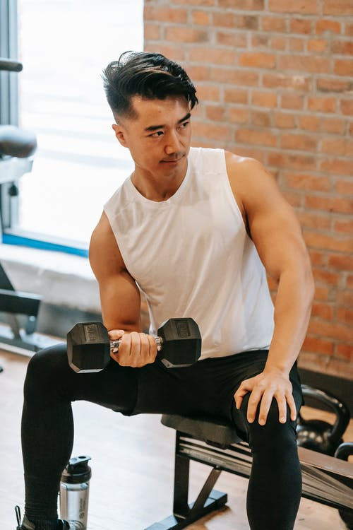 Sportive Asian male in sportswear pumping bicep with dumbbell while sitting on bench in fitness studio with brick wall during workout
