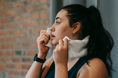 Ethnic woman with towel exercising in gym