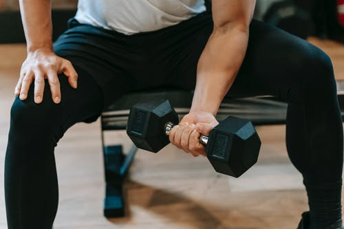 Crop man lifting dumbbell on bench