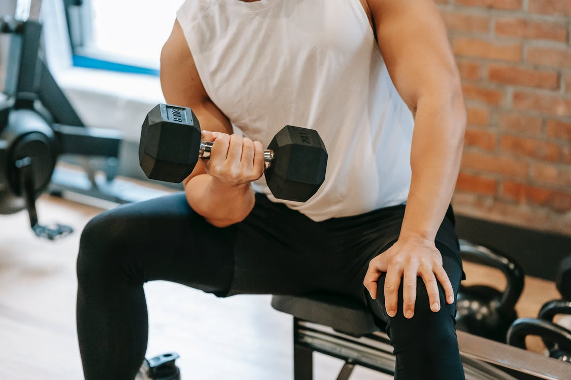 Unrecognizable strong male pumping bicep while lifting heavy metal dumbbell in modern fitness studio with sportive equipment near brick wall