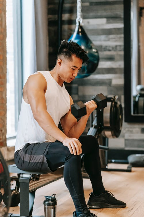 Fit Asian man exercising with dumbbell in gym