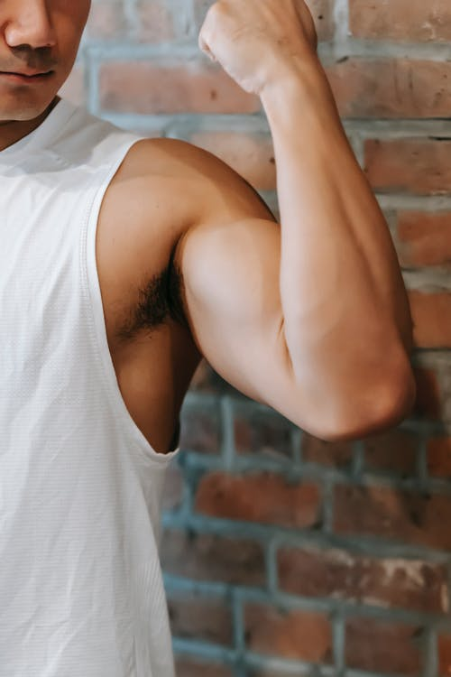 Crop anonymous sporty fit male demonstrating strong arm with bicep near brick wall