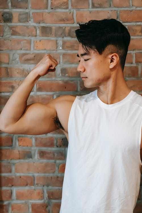 Young ethnic powerful male demonstrating strong bicep on arm near brick wall of gym