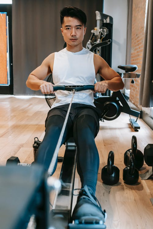 Concentrated young ethnic male working out with gym rowing machine near heavy kettlebells in sport club