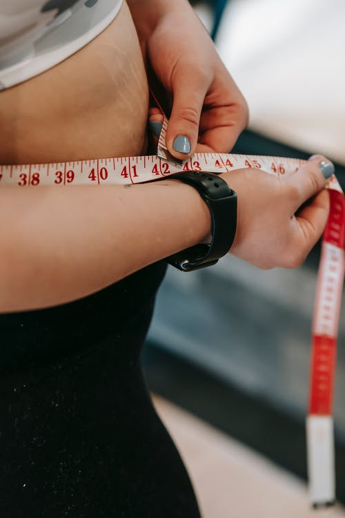 Crop anonymous female with measuring tape around big belly on blurred background of gym