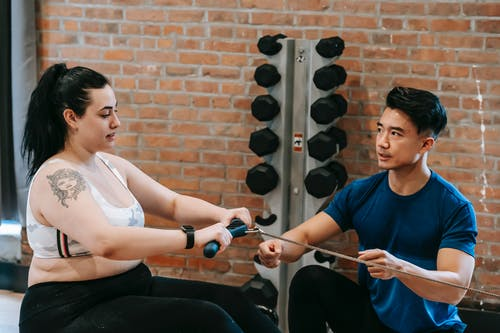 Multiethnic trainer and overweight woman doing exercises with rowing machine together in sport club
