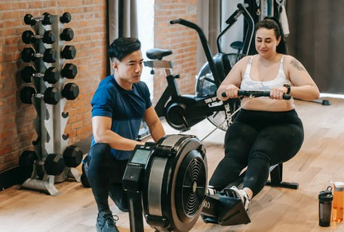 Positive young plus size female in leggings and crop top doing abs exercise on rowing machine during intense workout in modern gym with fit Asian male trainer