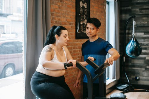 Young concentrated plus size lady in sportswear training on cycling machine during cardio workout in modern fitness club with ethnic male personal trainer