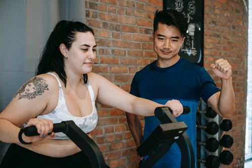 Smiling young tattooed plus size sportswoman in activewear doing cardio exercise on fitness cycle while training in contemporary gym with positive Asian male instructor