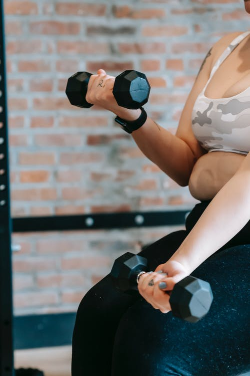 Side view of crop anonymous plus size woman in activewear lifting dumbbells during weight lose training in modern sports center