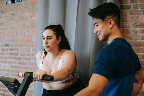 Side view of positive young Asian male trainer supporting plus size female doing cardio workout on cycling machine in modern fitness center