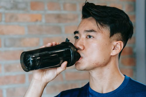 Side view of concentrated young ethnic male athlete drinking bottle of water during workout in gym