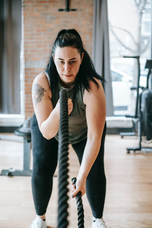 Determined young obese woman working out with battle ropes in gym