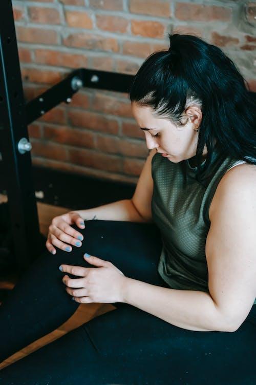Tired woman in sportswear resting in gym