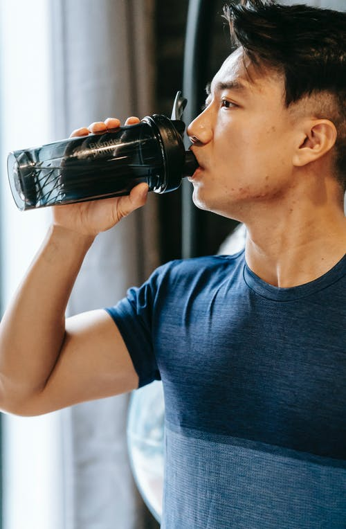 Serious ethnic man in sportswear drinking water from plastic bottle during break in fitness workout in gym